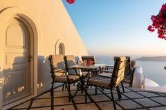 Patio z stołem i krzesłami dekorował z pięknymi bougainvillea kwiatami przy Santorini wyspą, Grecja fotografia royalty free