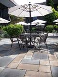 Patiohof mit Tabelle, Stühlen und weißen Regenschirmen Lizenzfreie Stockfotos