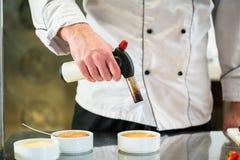 Patissier lub szefa kuchni płonącego creme brulee robi deser obrazy stock
