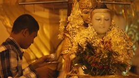 Patiti buddisti che bagnano la statua di Buddha per le benedizioni a Shwedagon stock footage