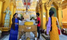 Patiti buddisti che bagnano le statue di Buddha alla pagoda di Shwedagon Immagini Stock