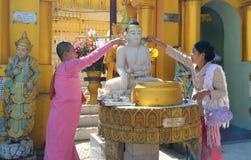 Patiti buddisti che bagnano le statue di Buddha alla pagoda di Shwedagon Fotografia Stock