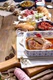 Pato cozido e vários petiscos para a tabela do Natal Tabela rústica com decoração e alimento diferente para o feriado Vista super foto de stock royalty free