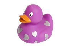 Pato de borracha roxo com os corações prateados isolados sobre o branco Fotografia de Stock