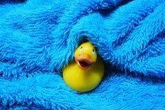 Pato de goma en una toalla azul Foto de archivo
