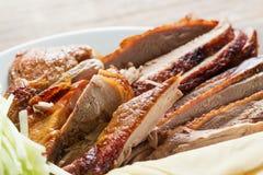 Pato de Pekín - pato de carne asada chino con los pedazos del pepino en el cierre blanco de la placa para arriba Fotografía de archivo libre de regalías