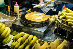 PATONG BEACH, THAILAND - 19 MAY 2017: Nightlife in Thailand. Street food. A prepares a pancake with chocolate in the. PATONG BEACH, THAILAND - 19 MAY 2017 Royalty Free Stock Images