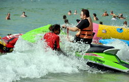 Patong, Thailand: Man on a Jet Ski. A large Adaman sea wave crashes over a man on a jet ski boat as an instructor teaches him how to operate it at Patong Beach Royalty Free Stock Photography