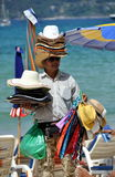 Patong, Thailand: Man Selling Hats on Beach. A vendor walking along the beach with dozens of hats stacked on his head and hands sells them to beach goers to help Stock Images