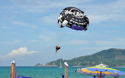 PATONG, THAILAND: Paragliding on the Beach. Woman with her accompanying Thai flyer swoop down over the sea for a landing on Patong Beach after a high-flying five Stock Images