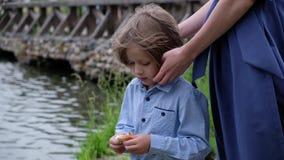 Patos de alimentación del niño pequeño por el río Madre que frota ligeramente el pelo del niño Verano al aire libre Cierre para a almacen de metraje de vídeo