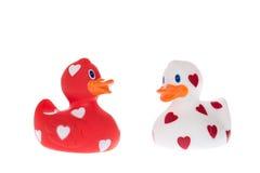 Patos de goma rojos y blancos con los corazones Foto de archivo