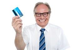 Patrón envejecido alegre que soporta una tarjeta de débito imagenes de archivo