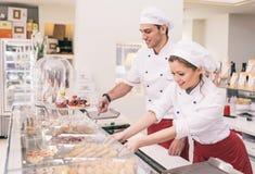 Patrón y mujer de negocios felices en una tienda de pasteles imágenes de archivo libres de regalías