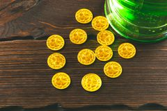Patrick`s day background with a Glass of green beer and clover gingerbread with gold coins on wooden Royalty Free Stock Photo