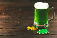 Patrick`s day background with a Glass of green beer and clover gingerbread with gold coins on wooden Stock Photo