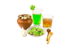 Patrick`s Day celebrations glass of whiskey scotch with three slices of ice a glass of green beer with garlic for a snack and a bi Royalty Free Stock Photography