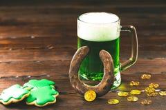 Patrick-` s Tageshintergrund mit einem Glas des grünen Bier- und Kleelebkuchens mit Goldmünzen auf hölzernem Stockfotos