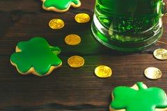 Patrick-` s Tageshintergrund mit einem Glas des grünen Bier- und Kleelebkuchens mit Goldmünzen auf hölzernem Stockbilder