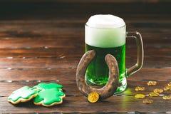 Patrick-` s Tageshintergrund mit einem Glas des grünen Bier- und Kleelebkuchens mit Goldmünzen auf hölzernem Lizenzfreie Stockfotos