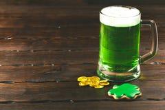 Patrick-` s Tageshintergrund mit einem Glas des grünen Bier- und Kleelebkuchens mit Goldmünzen auf hölzernem Stockfoto