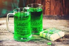 Patrick `s Tageshintergrund Zwei Becher des grünen Bieres, des Imbisses und der Geschenkbox für Feier Partei für St Patrick Tag K lizenzfreie stockbilder