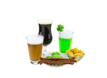 Patrick saint day beer tasting glass of green wheat lager and a glass of dark stout snack biscuits clover. Celebration Patrick saint day beer tasting glass of Royalty Free Stock Photo