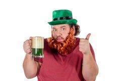 Patricks dagparti Stående av den roliga feta mannen som rymmer exponeringsglas av öl på St Patrick arkivbild