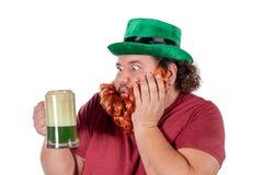 Patricks dagparti Stående av den roliga feta mannen som rymmer exponeringsglas av öl på St Patrick royaltyfri foto