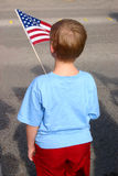 Patriot. Young boy holding American flag while waiting for the parade Royalty Free Stock Image