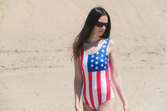 Patriot beautiful woman walking on the beach in July Stock Images