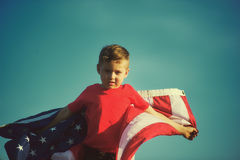Patriot boy with the US flag. Happy boy with the American flag. Patriotic holiday. Flag of the USA Stock Images