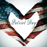 Patriot day. Written in the blank space of a heart sign made with the hands patterned with the colors and the stars of the United States flag stock photos
