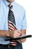 Patriot Voter Takes a Poll. Patriotic voter wearing a U.S. flag tie and dress shirt sporting an I voted sticker takes a poll Stock Images