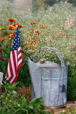 Patriotic. Flower arrangement. Baby's breath in a watering can with a flag beside it stock photography
