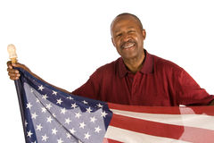 Patriotic African American man. Senior African American man, holding an American flag, he is smiling at the camera stock photo