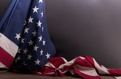 American flagged draped over itself with a black background. Patriotic American flag beautifully draped over itself in front of a marble-gray background with royalty free stock photo