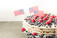 Patriotic American flag cake with blueberries and strawberries on vintage white background Royalty Free Stock Photography