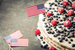 Patriotic American flag cake with blueberries and strawberries on vintage white background royalty free stock photos