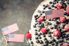 Patriotic American flag cake with blueberries and strawberries on vintage white background Royalty Free Stock Images