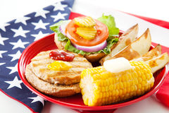 Patriotic American Turkey Burger. Healthy turkey burger on whole grain bun, with baked potato wedges and corn on the cob. Low fat picnic on an American Flag stock photos