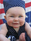 Patriotic Baby. Adorable baby girl with blue and white dress and American flag background Stock Photos