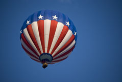 Patriotic balloon. American Flag colored balloon soaring in a clear blue sky Royalty Free Stock Photo
