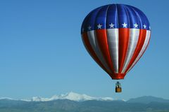 Patriotic Balloon Over the Rockies. A red, white and blue hot air balloon floats above the Rocky Mountains Stock Photos