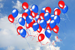 Patriotic balloons. Red and blue balloons airborne in summer sky Stock Images