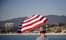 Patriotic Beachwear. A man wearing patriotic garb / matching bandanna and umbrella Stock Images