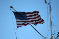 Patriotic Boat Mast. American flag attached to a sailboat mast and rippling in the wind royalty free stock image