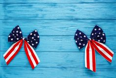 Patriotic bows as decorations for 4th of July day of American independence. USA holiday decorations on blue wooden background. Top view, flat lay royalty free stock photo