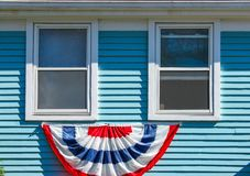 Patriotic bunting displayed beneath two wood windows on a blue painte house for Memorial Day or the 4th of July USA. Patriotic bunting displayed beneath 2 wood Stock Images
