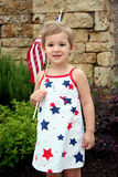 Patriotic Child. A little girl shows her patriotism to the USA on July 4th holding a flag and wearing a red, white and blue dress Royalty Free Stock Photo